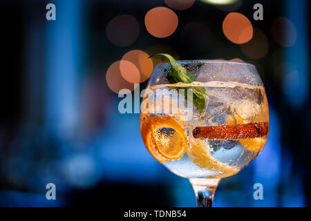 Beautiful glass of gin on bar counter with blurred background in shades of blue and boke. - Stock Photo