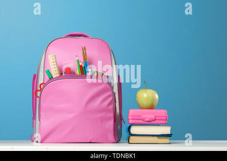 Student set. Pink backpack with stationery, a stack of books, a lunchbox, an apple on the table on a blue background. Back to school. - Stock Photo