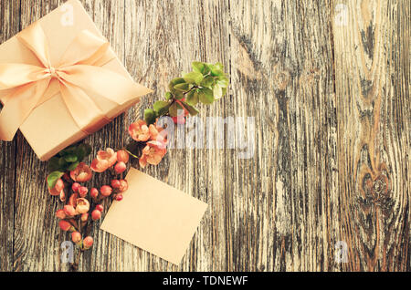 Gift craft paper box with bow ribbon and blank tag. Flat lay composition for birthday, mother day or wedding with delicate flowering branch. Vintage g - Stock Photo