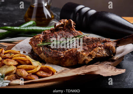 Tomahawk steak with vegetables and a knife on the table. Grilled meat with grilled vegetables and fresh vegetables on the table. - Stock Photo