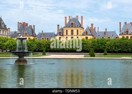 Fountain and pond in the Grande Parterre of Château de Fontainebleau, Seine-et-Marne, Île-de-France region of France - Stock Photo