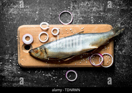Salted herring on a wooden cutting Board with onion rings. On dark rustic background - Stock Photo