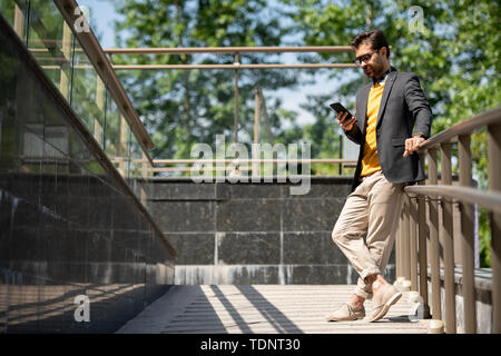 Young casual man in beige jeans, yellow pullover and dark blue jacket scrolling in smartphone by railings outdoors - Stock Photo