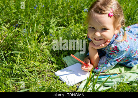 Little happy girl 4-5 years old lies on the green grass. Painting a little funny girl - Stock Photo