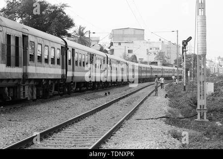 BANGALORE INDIA June 1, 2019 :Monochrome image of People standing on edge of the staircase steps of moving Train at Bengaluru due to non availablity o - Stock Photo