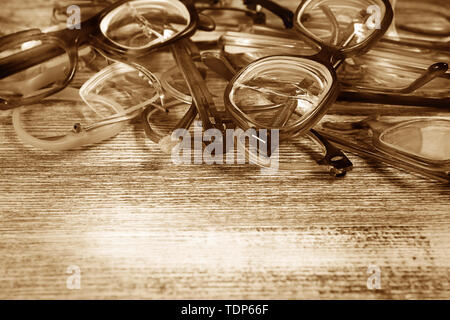 Several broken eyeglasses on the wooden background and text space - Stock Photo