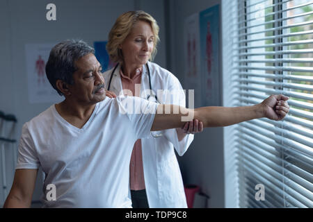 Female doctor examining male patient arm in hospital - Stock Photo