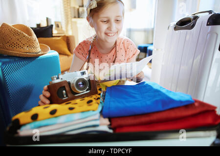 happy modern tourist girl with retro film camera and map with open suitcase ready for vacation in the modern living room in sunny summer day. - Stock Photo