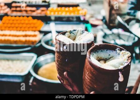 Two ceramic filled with Lasse, a traditional Indian yogurt drink in a food market - Stock Photo