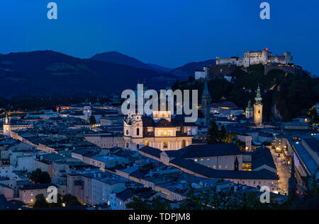Salzburg Cityscape at Sunset, with Salzburg Cathedral and Hochensalzburg Fortress on top of the Hill. Photo was taken in summer - Stock Photo