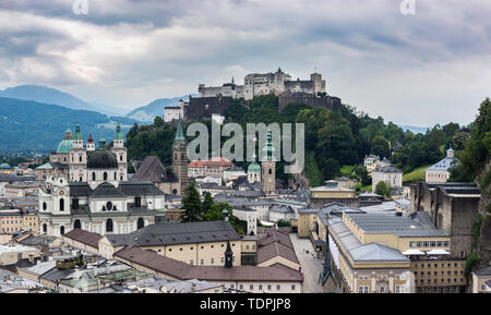 Salzburg Cityscape with Salzburg Cathedral and Hochensalzburg Fortress on top of the Hill. Photo was taken in summer - Stock Photo
