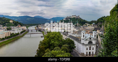 Salzburg Cityscape with Hochensalzburg Fortress on top of the Hill. Photo was taken in summer - Stock Photo