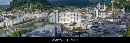 Panoramic view of the Salzburg Cityscape, with the Salzach river on the left and the Salzburg Cathedral on the right side. Photo was taken in summer - Stock Photo