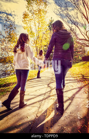 A mother and her two daughters walking and talking on a pathway in a city park on a warm autumn day; Edmonton, Alberta, Canada