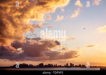 Miami Florida Biscayne Bay downtown city skyline high rise buildings clouds storm front sunset jet plane commercial airliner reflected light - Stock Photo