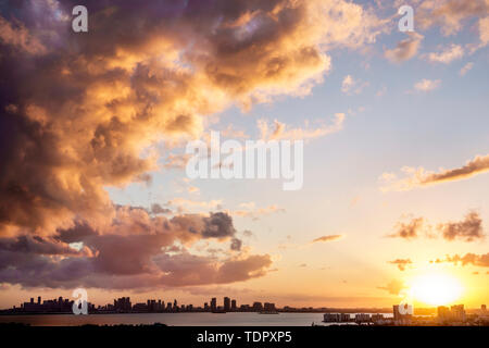 Miami Florida Biscayne Bay downtown city skyline high rise buildings clouds storm front sunset reflected light - Stock Photo