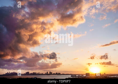 Miami Florida Biscayne Bay downtown city skyline high rise buildings clouds storm front sunset jet reflected light - Stock Photo