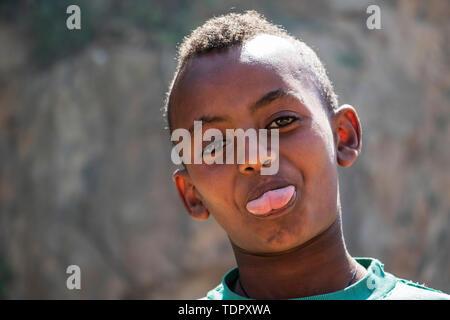Eritrean boy sticking out his tongue for the camera; Arbaroba, Central Province, Eritrea - Stock Photo