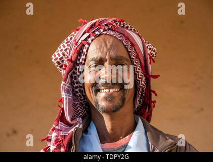 Portrait of an Eritrean man smiling with a headscarf on his head, Monday livestock market; Keren, Anseba Region, Eritrea - Stock Photo