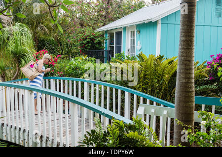 Captiva Island Florida 'Tween Waters Inn Island Resort & Spa hotel garden cottage bungalow wooden bridge woman looking - Stock Photo