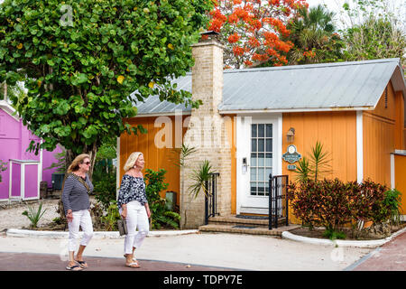 Captiva Island Florida 'Tween Waters Inn Island Resort & Spa hotel guest cottage exterior chimney tropical foliage woman strolling friends - Stock Photo