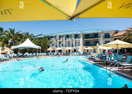 Captiva Island Florida 'Tween Waters Inn Island Resort & Spa hotel pool lounge chairs man woman swimming guest - Stock Photo