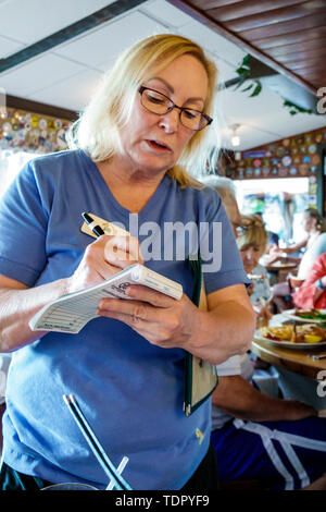 Captiva Island Florida The Mucky Duck restaurant inside woman waitress writing food order - Stock Photo