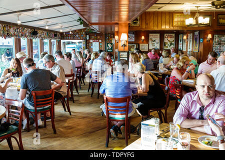 Captiva Island Florida The Mucky Duck restaurant inside tables crowded busy casual dining man woman - Stock Photo