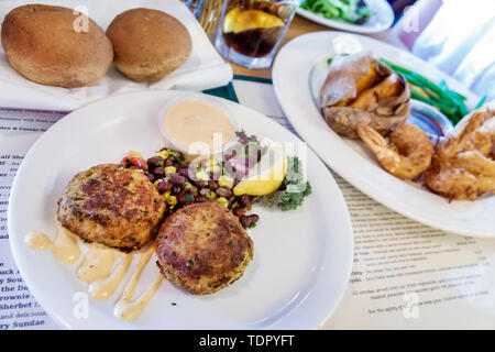 Captiva Island Florida The Mucky Duck restaurant dinner plates meal food crab cakes rolls fried shrimp - Stock Photo