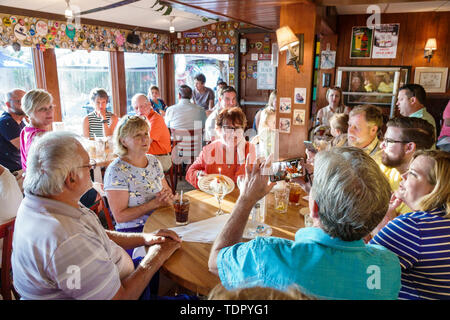 Captiva Island Florida The Mucky Duck restaurant inside tables crowded busy casual dining man woman birthday celebration taking photo smartphone - Stock Photo