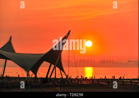 Summer sunset. The summer day on the Yantai golden beach beach beach is crowded, the seaside is cool, and the setting sun reflects the sky and the sea. - Stock Photo