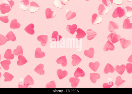 Heart shape confetti on pink pastel holiday background. Festive abstract backdrop, Valentine's Day, Love. Flat lay. - Stock Photo
