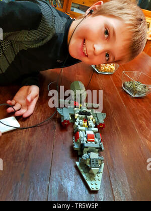 boy building a starship with LEGO listening to music, Germany - Stock Photo