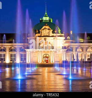 illuminated Kaiserpalais with mit water columns in the spa park at blue hour, Germany, North Rhine-Westphalia, East Westphalia, Bad Oeynhausen - Stock Photo