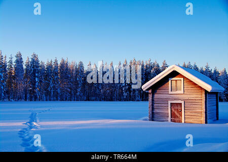 wooden house in winter in evening light, Finland, Lapland - Stock Photo
