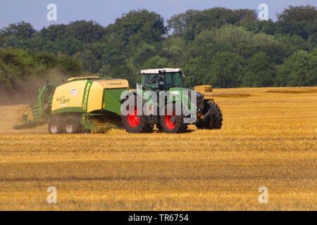 baler on harvested cornfield, Germany - Stock Photo
