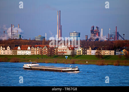 cargo ship on river Rhine, buildings and Thyssenkrupp industrial scenery in background, Germany, North Rhine-Westphalia, Ruhr Area, Duisburg - Stock Photo