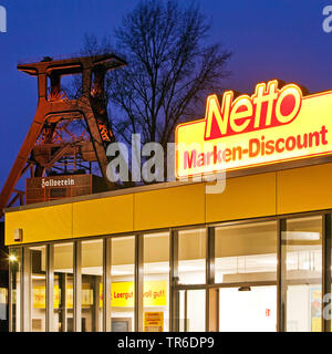 coalmine Zollverein with head gear Schacht XII in the evening with Netto market, Germany, North Rhine-Westphalia, Ruhr Area, Essen - Stock Photo