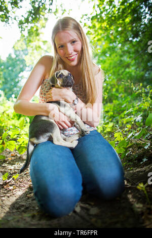domestic dog (Canis lupus f. familiaris), good looking young woman with a Puggle in arm, kneeing on forest ground, Germany - Stock Photo
