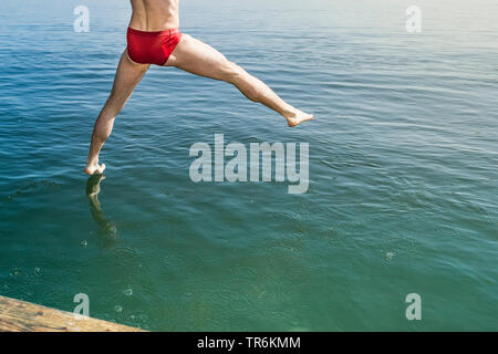 young man in red bathing trunks juming into lake Lake Starnberg, Germany, Bavaria - Stock Photo