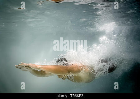 young man diving in a swimming pool, Germany - Stock Photo