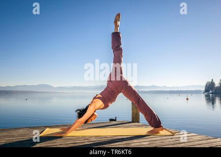 woman doing yoga exercises at a lake. leg high, downward facing dog, Germany, Bavaria - Stock Photo