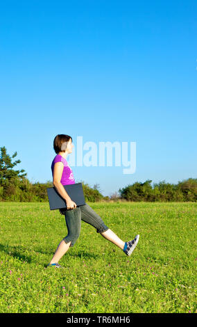 teen girl walking with notebook across a meadow, Germany - Stock Photo