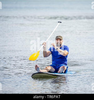 bearded man paddling in the ocean, Germany - Stock Photo