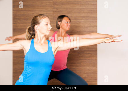 two women doing yoga in the living room at home, warrior - Stock Photo