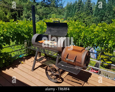 grill meat in a Barbecue-Smoker on a terrace, Germany - Stock Photo