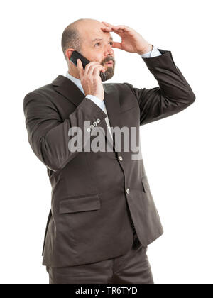 Middle-aged businessmann calling with his phone near his ear, Germany - Stock Photo