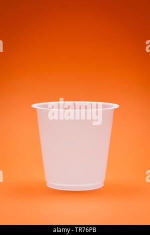 white empty plastic cup on an orange background - Stock Photo