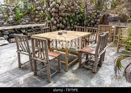 Wooden table and chairs in empty beach cafe next to sea in garden. Close up. Island Koh Phangan, Thailand - Stock Photo
