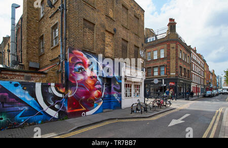 LONDON SPITALFIELDS BRICK LANE AREA GAFFITI AND WALL ART IN HANBURY STREET AND SEVERAL BRICK HOUSES - Stock Photo